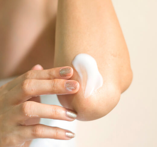 A woman rubbing cream over dry skin on elbow